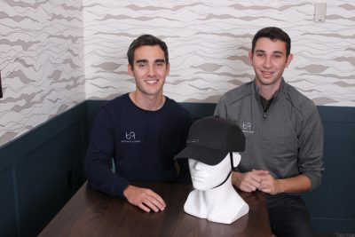 Two young men sit at a table and pose for a photo. 上 the table is a white mannequin head and neck, wearing a black helmet that looks like a baseball cap.