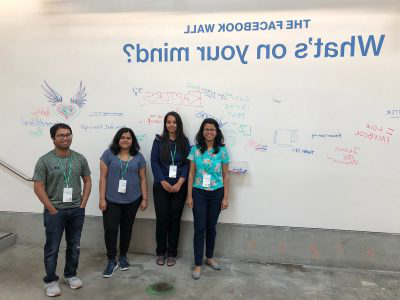 Tanushree Mitra and her students standing in front of The Facebook的 Wall