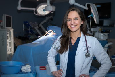 Woman wearing medical white coat standing in dimly lit operating room